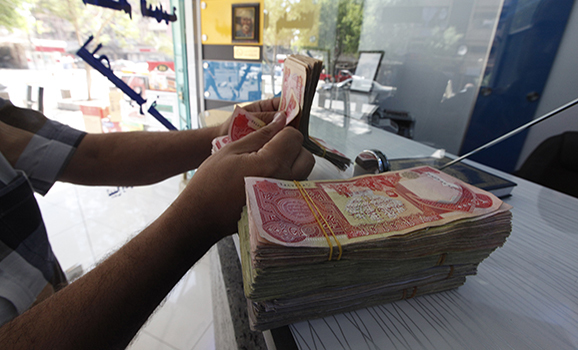 A customer counts Iraqi dinars at a money changer in Baghdad